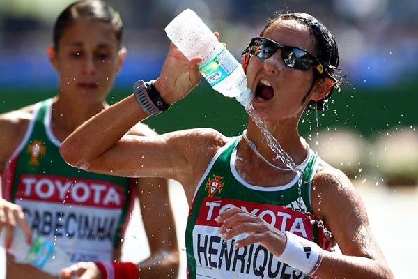 Ines Henriques (R) of Portugal uses water to cool down in front of Ana Cabecinha of Porotugal during the women's 20km race walk  (Getty Images)